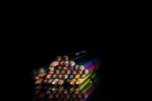 stack of colored pencils on a black background with copy space