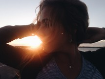 a woman with her hands behind her head walking near a beach at sunset