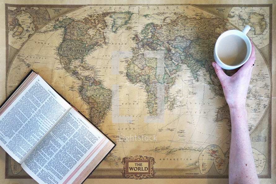 woman reaching for a mug with a Bible on a world map