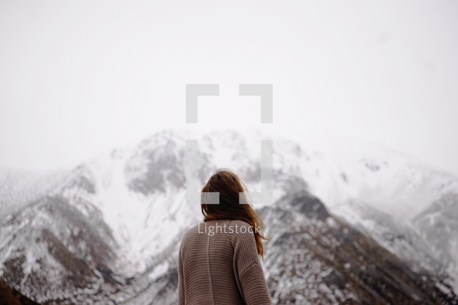 a woman looking up a snow covered mountain peak
