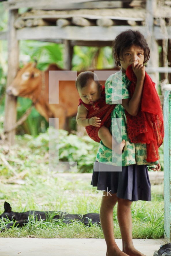 a girl standing barefoot with a baby on her back
