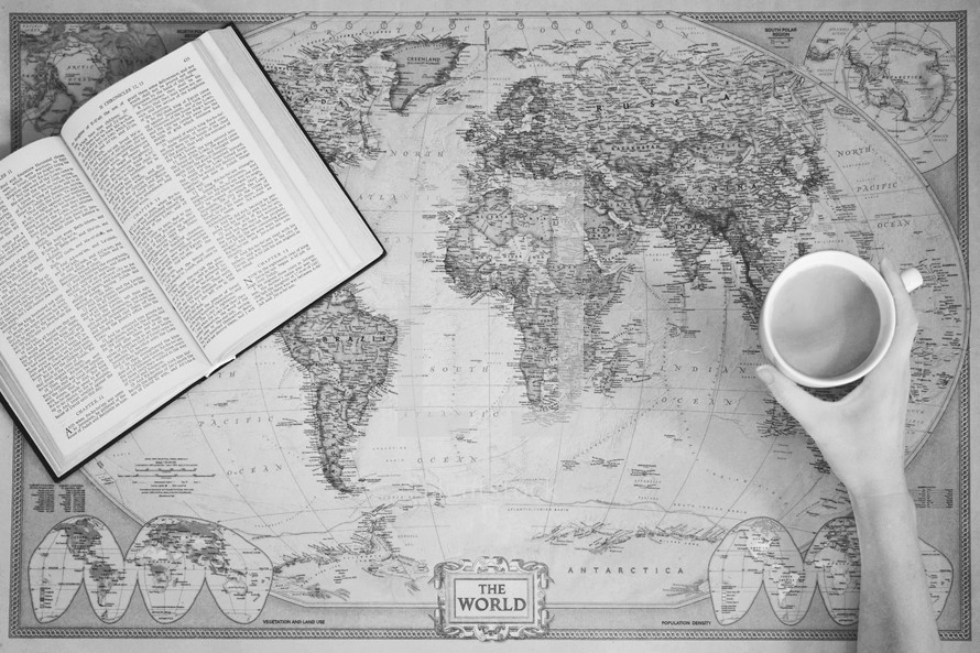 Bible and mug on a world map
