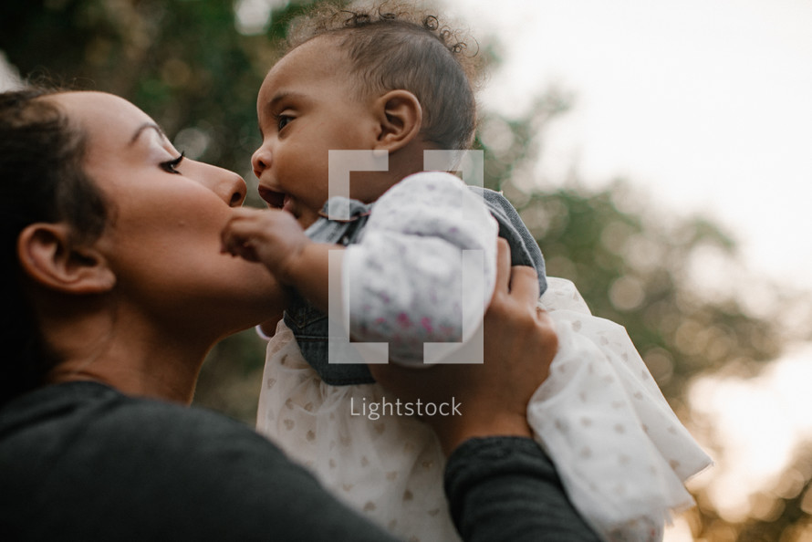 a mother holding up and kissing her infant daughter