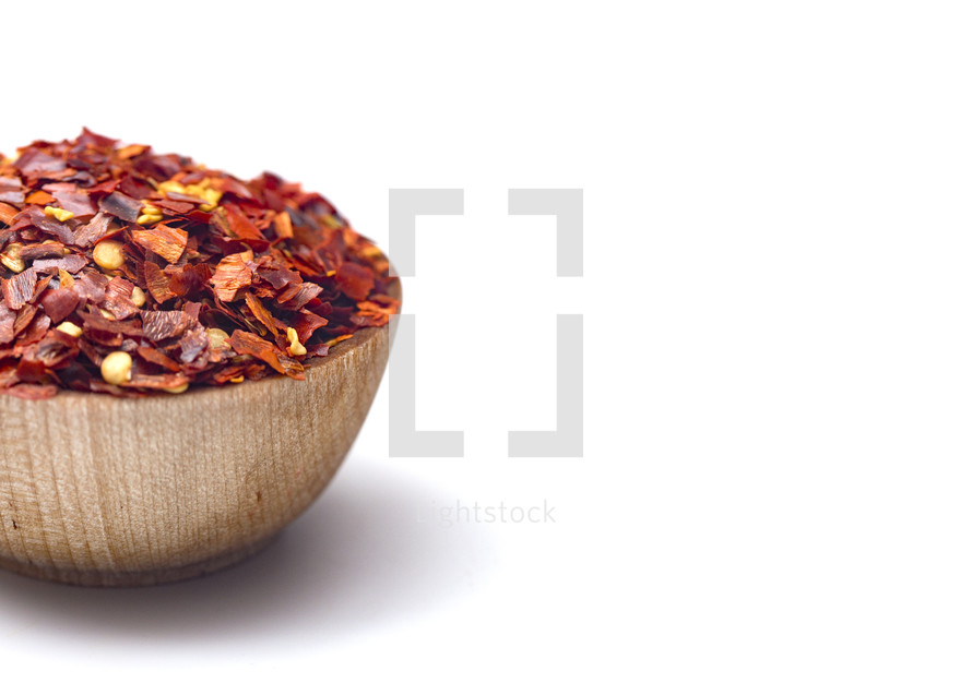Crushed Red Pepper in a Wooden Bowl on a White Background