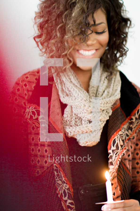 A young woman smiling and holding a candle