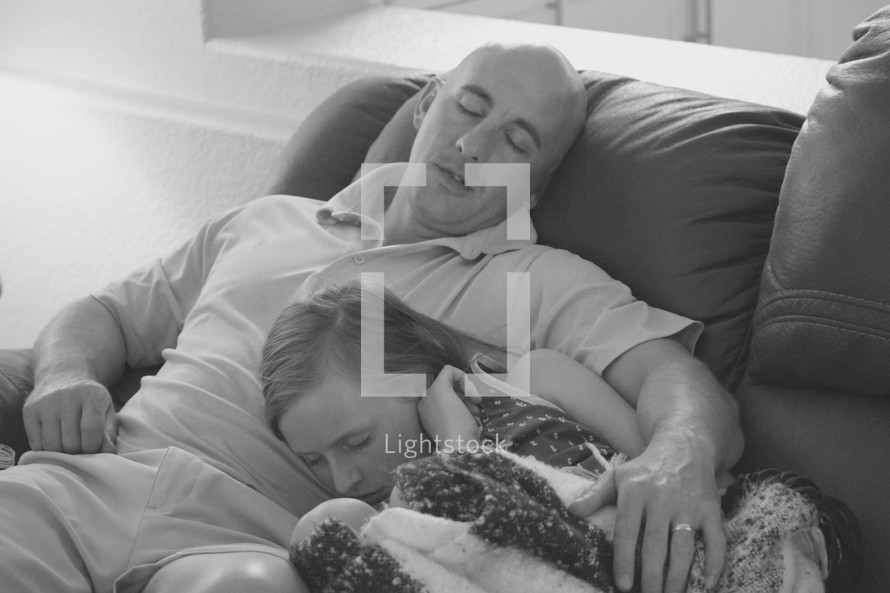 father and daughter asleep on the couch after a long week