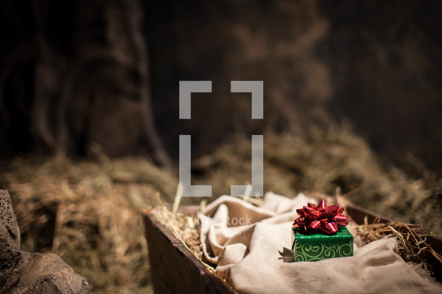 Green wrapped box with red bow on linen cloth in basket of hay.
