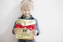 A child holding a Christmas gift for Dad