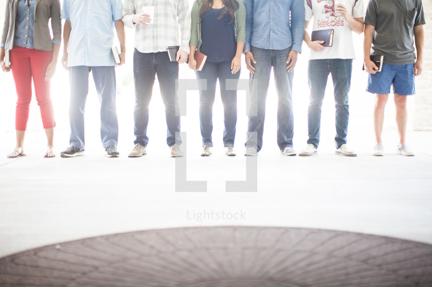 legs of men and women standing holding Bibles