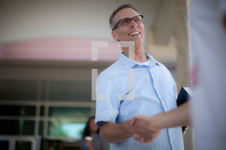 man welcoming and shaking hands at a church entrance