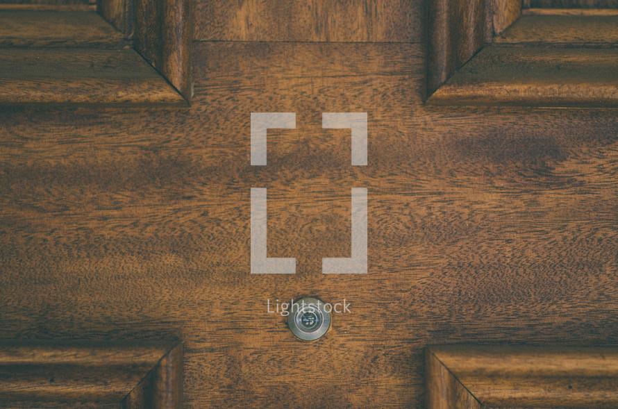 Peep hole in a wooden door.