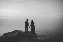 silhouette of a couple holding hands by a shore