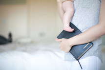 Mother holding infant child and a Bible.