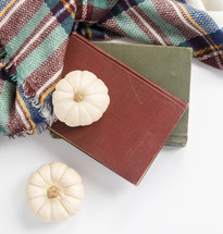 white pumpkins, books, and plaid shawl