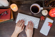 a woman's hands on a computer keyboard on a fall desk