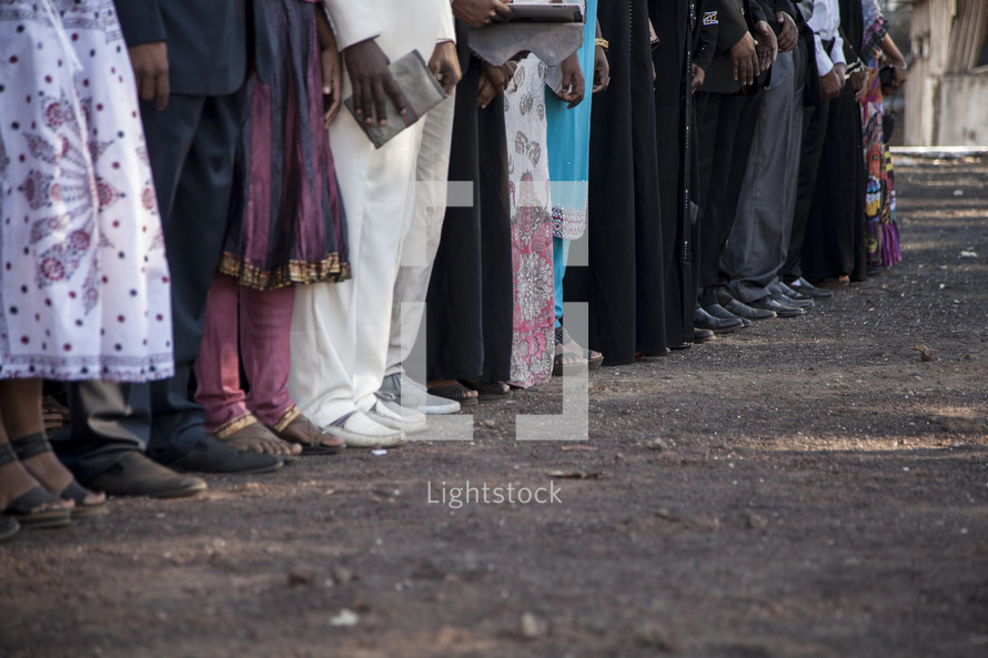 feet of family members gathered at a graduation ceremony in Africa