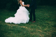 bride and groom holding hands standing in grass