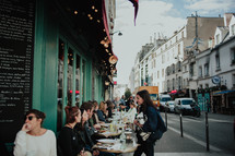 diners eating at outdoor seating at a cafe in Paris