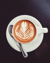 leaf design in creamer in a latte
