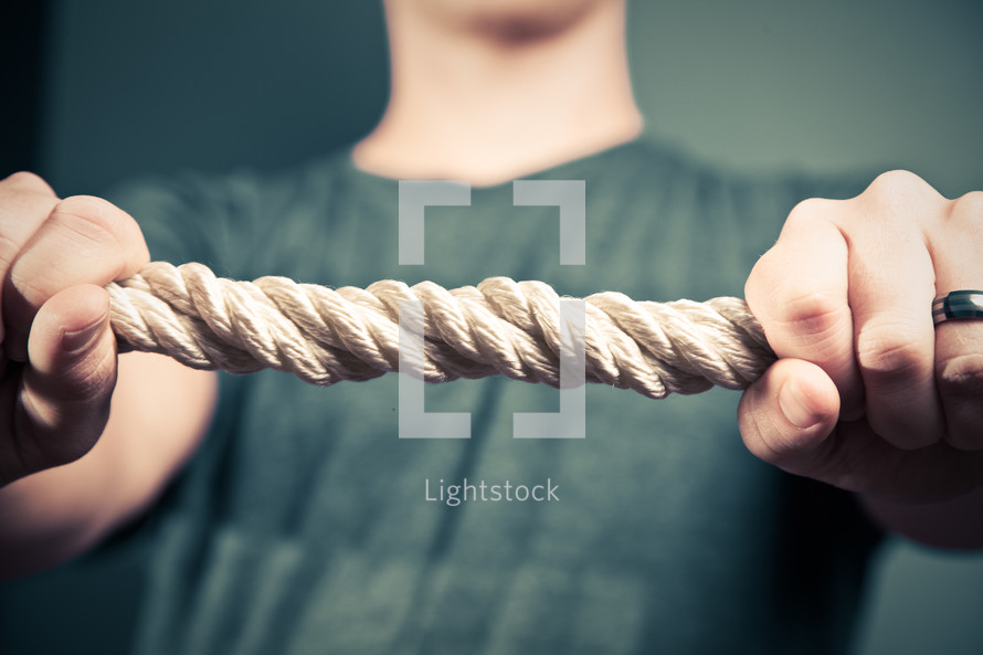man holding onto a thick rope