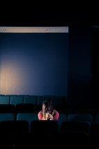 woman sitting in an empty auditorium with her head bowed in prayer