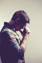 man in prayer with thumbs and index fingers against his forehead