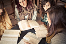 group of young women reading and discussing scripture at a Bible study