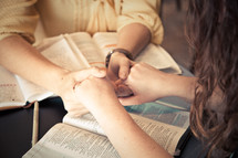 young women holding hands in prayer over Bibles