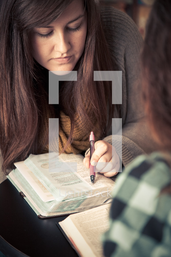 young woman pointing to scripture in a Bible