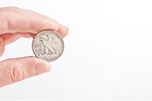 hand holding a half dollar coin