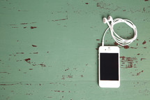 iPhone and earbuds on a painted wooden table top