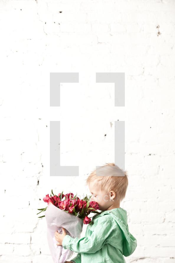 little boy holding a bouquet of flowers