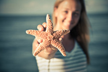 woman holding up a starfish on the beach