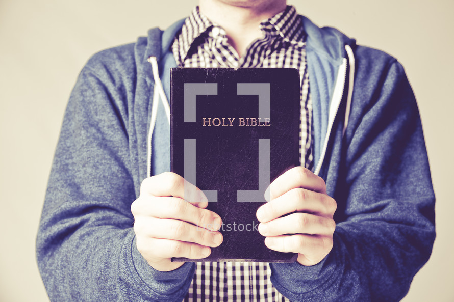 man holding up a black Holy Bible