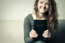 teen girl holding a Bible and smiling