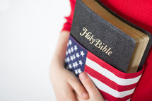 Holding a Holy Bible wrapped in an American flag.