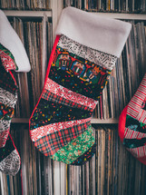 Christmas stockings hanging on a shelf full of vinyl records.