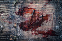 two bloody nails sit on an old wooden cross beam