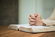 a woman with praying hands over an open Bible