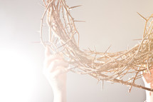 hand lifting up a crown of thorns