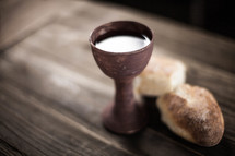 Communion bread and wine on a wood table.