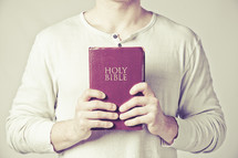man holding a red Holy Bible