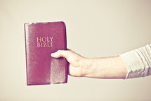 man holding a red covered Bible