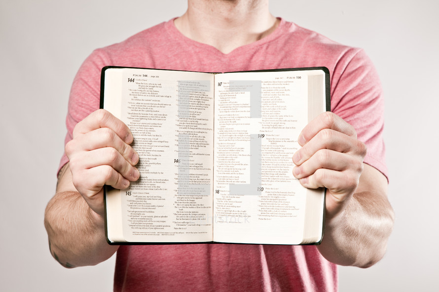 man holding a Bible showing its pages - Psalms 144-200