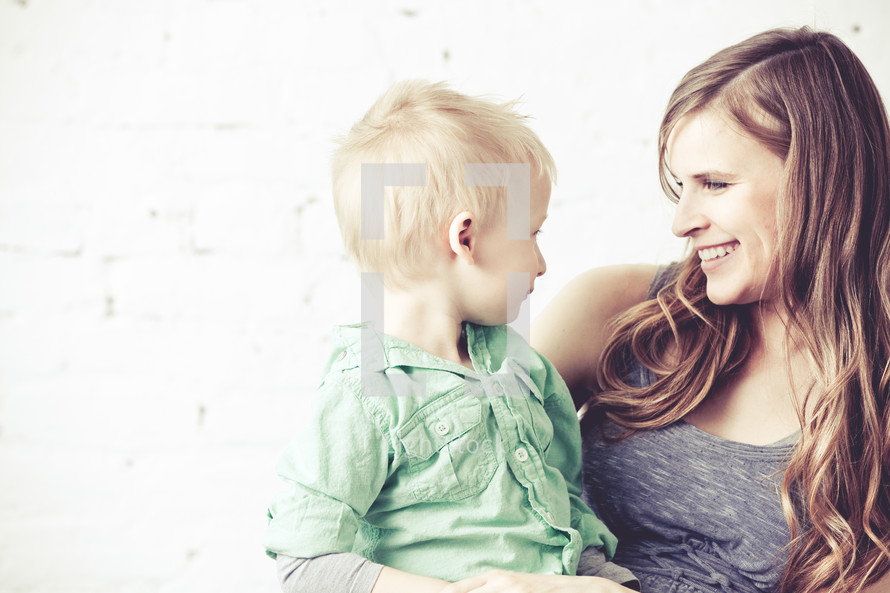 Smiling mother holding son in her lap.