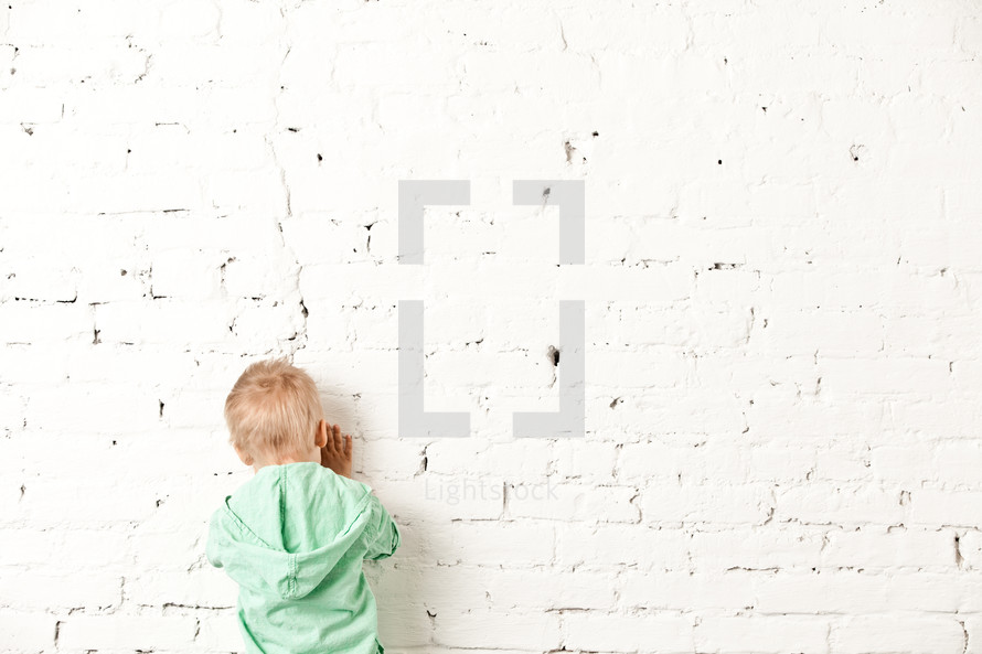 little boy facing a wall