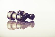 vintage binoculars with reflection on wood table