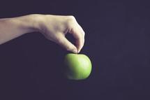 hand dangling a green apple