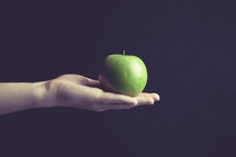 hand holding out a green apple