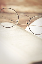 reading glasses on the pages of a Bible